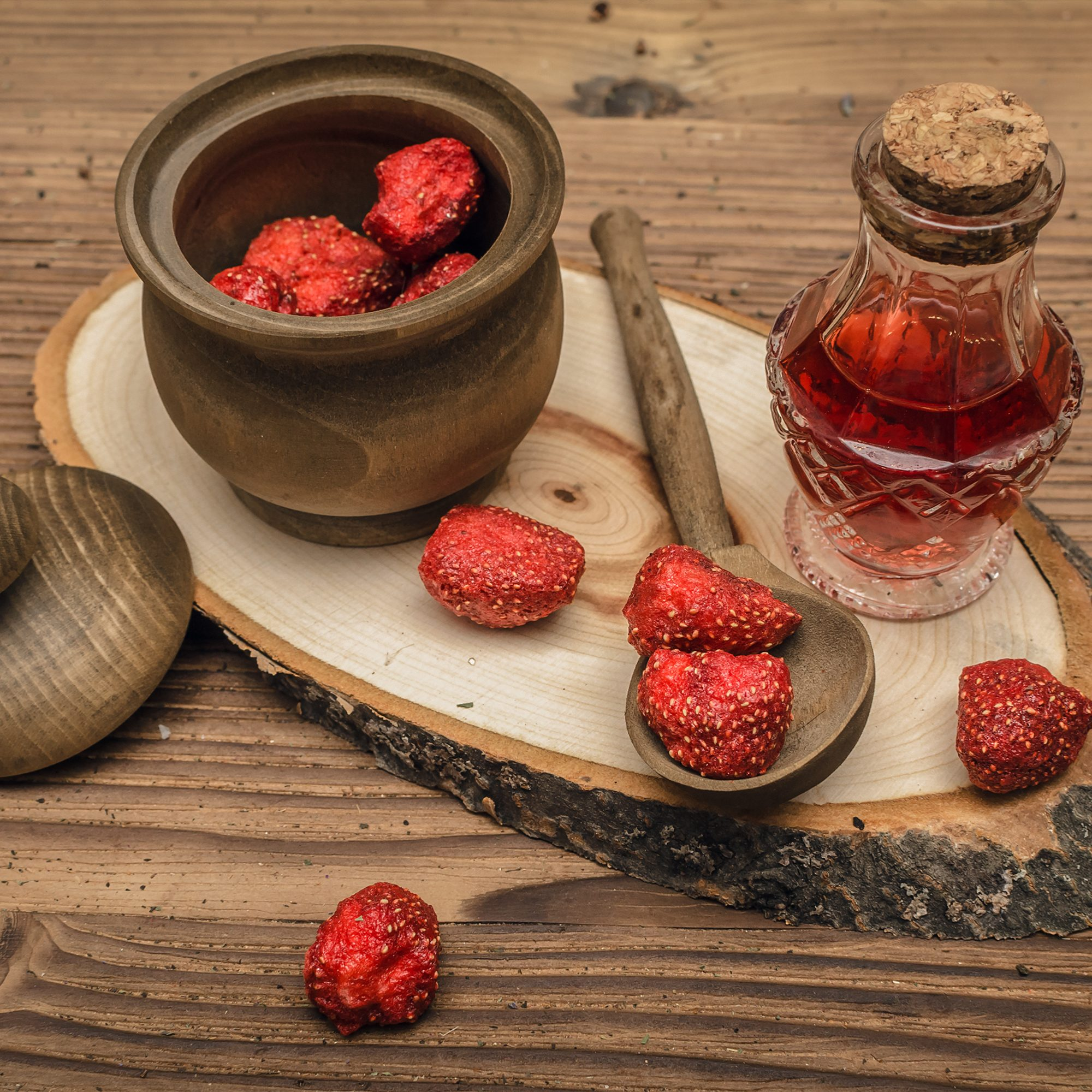 Herbal medicine concept. Dry strawberry in the jar and strawberry essential oil on wooden brown table. Organic ingredients.